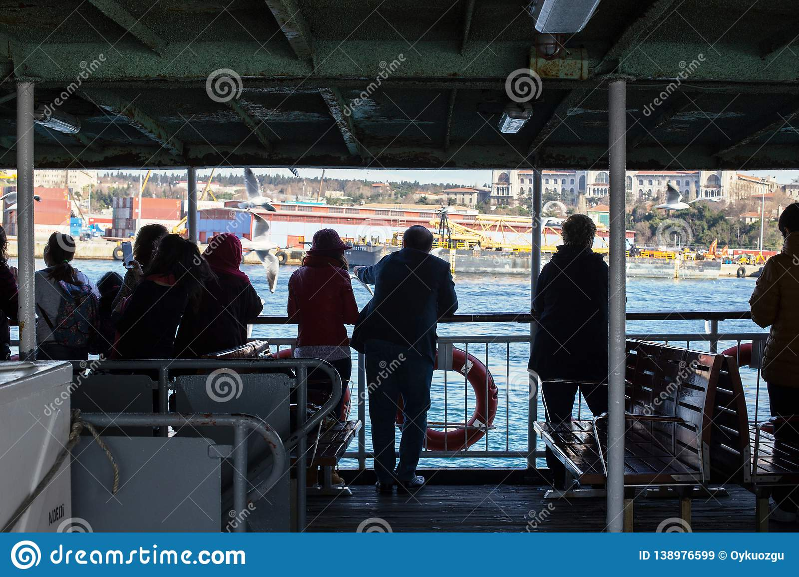 Island Ferry Ada Vapuru. Some of the ferry passengers feed seagulls. Passenger ferryboats from Istanbul sail regularly to the Pr. Istanbul / Turkey - 02/03/2016 royalty free stock images