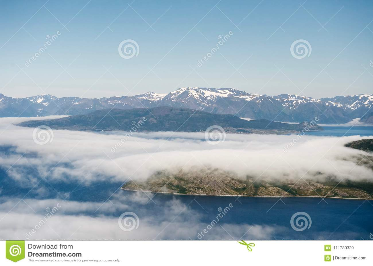 Islands covered by clouds into cold waters of norvegian fjord.