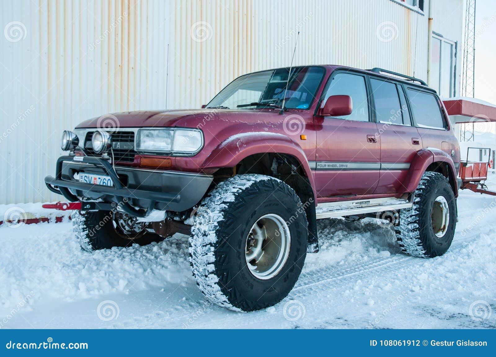 Islandzki zmodyfikowany Toyota ziemi krążownik na dużym toczy wewnątrz śnieg