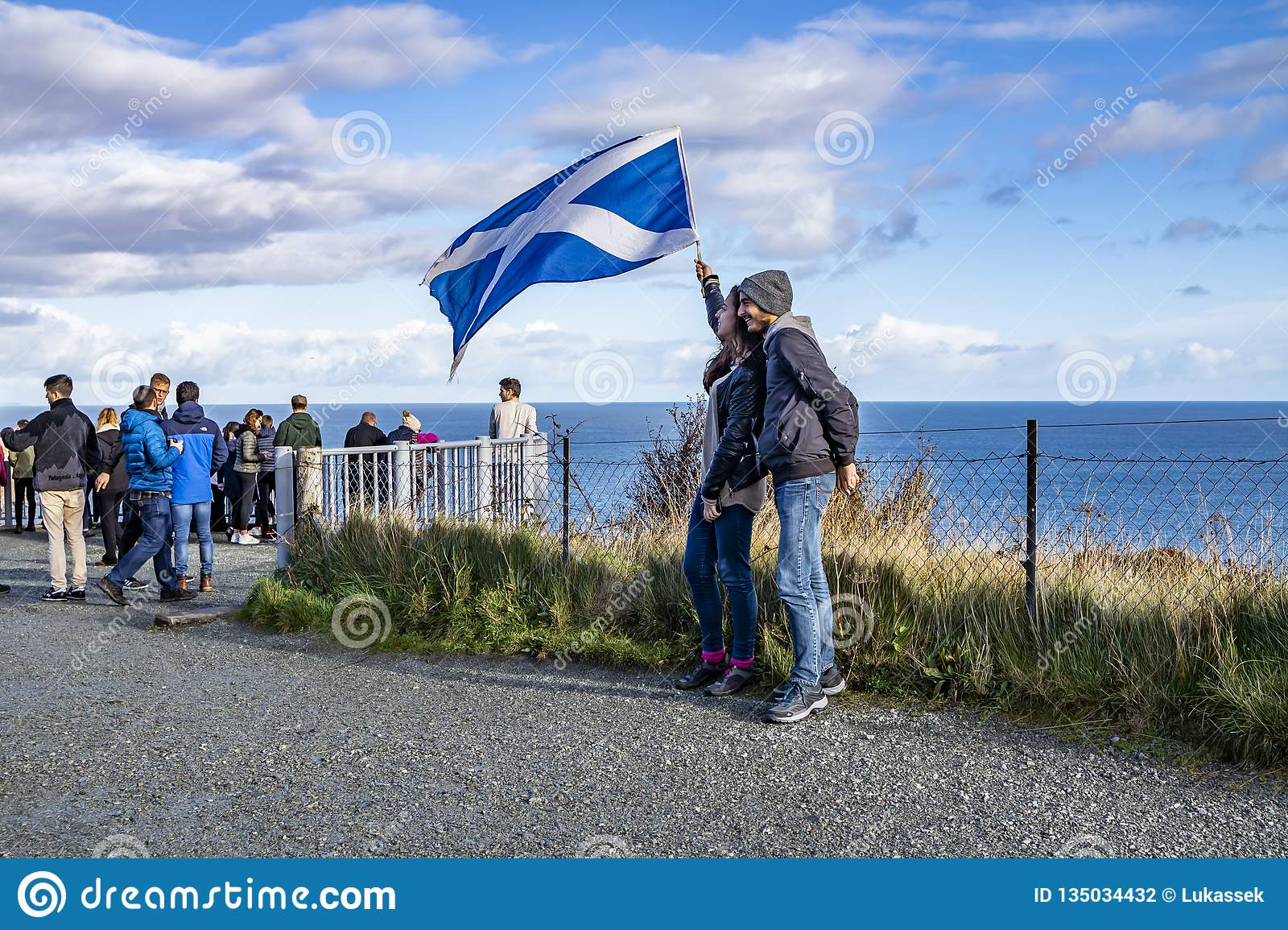 Isle of Skye , Scotland - October 14 2018 : Tourists visiting the Kilt Rock waterfall by Staffin with a waving flag