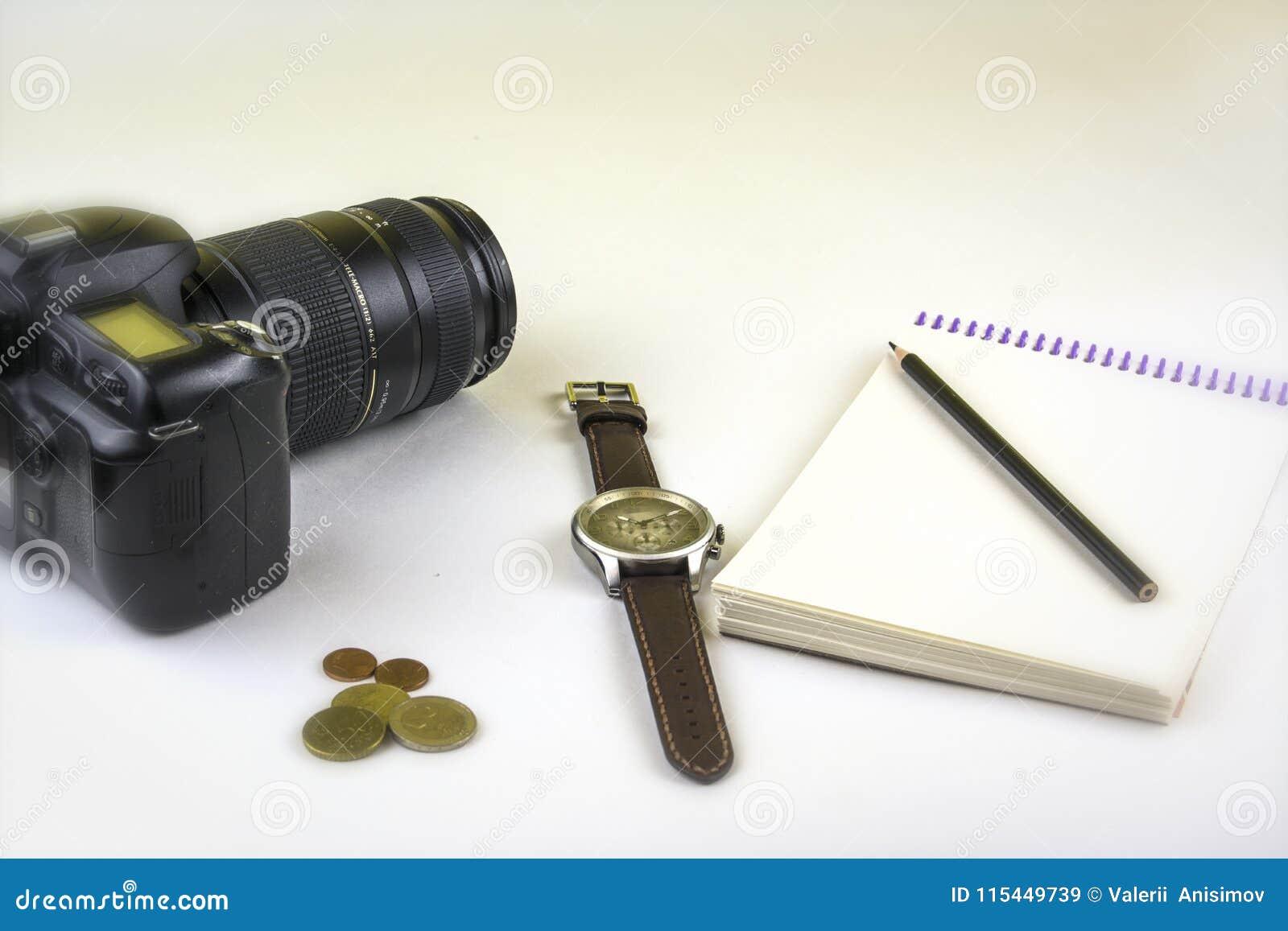 Isolat Appareil-photo, pièces de monnaie, crayon et bloc-notes de SLR sur le fond blanc