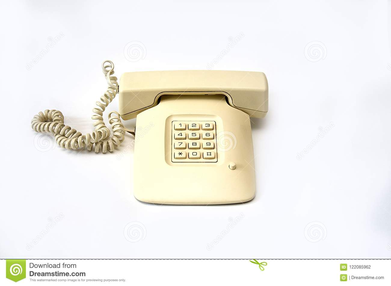 isolate beige old telephone with wire tube lies on white background Old Electric Wiring beige old telephone with a row lying off the removed wire tube isolate on a white background