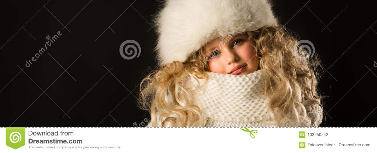 753459af194bf3 Isolated on black, beautiful caucasian blonde little girl in dark blue coat,  white scarf and white fur hat, look at camera