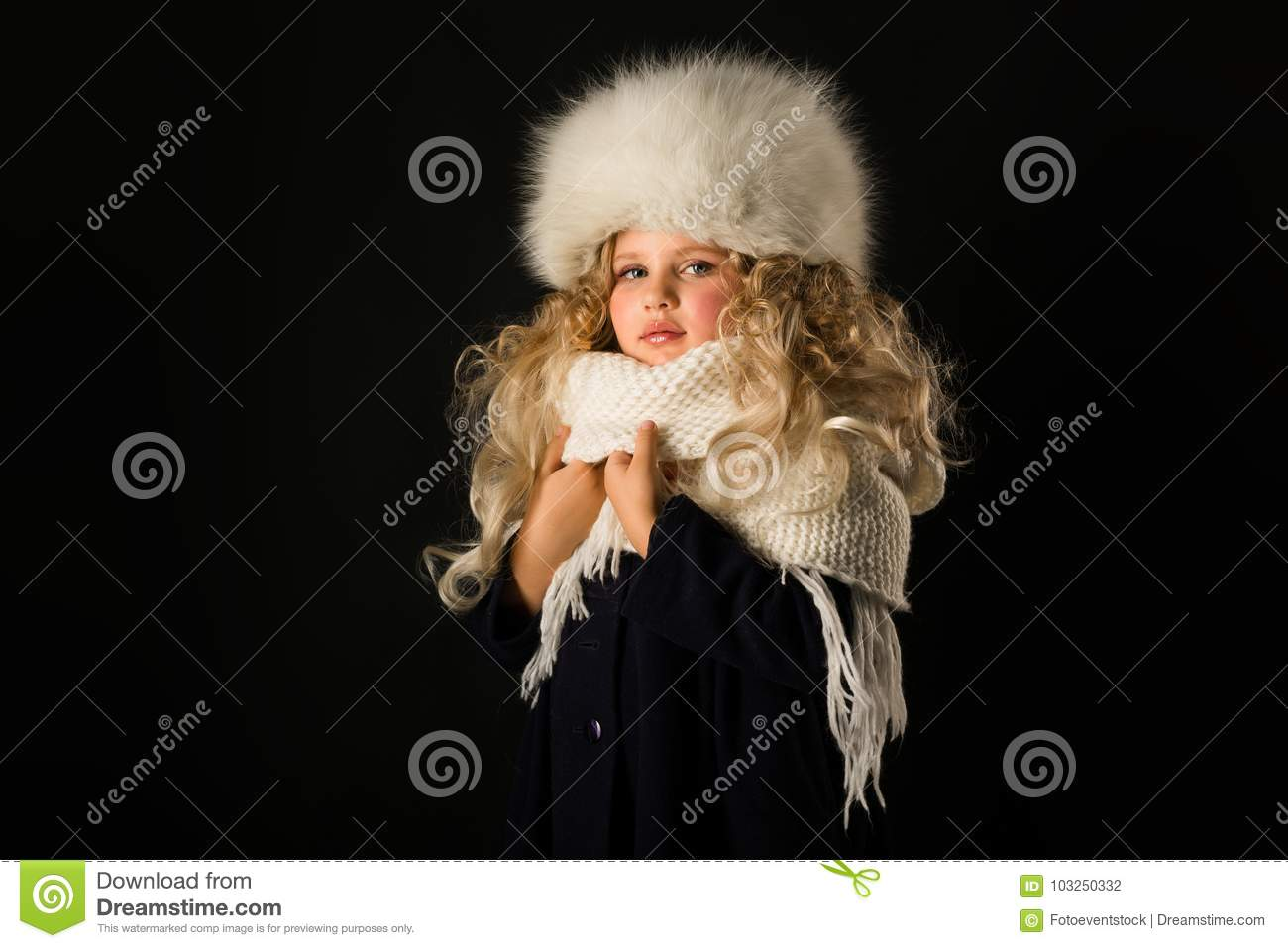 f8edbd15dba3d Isolated on black, beautiful caucasian blonde little girl in dark blue coat,  white scarf and white fur hat, look at camera. More similar stock images