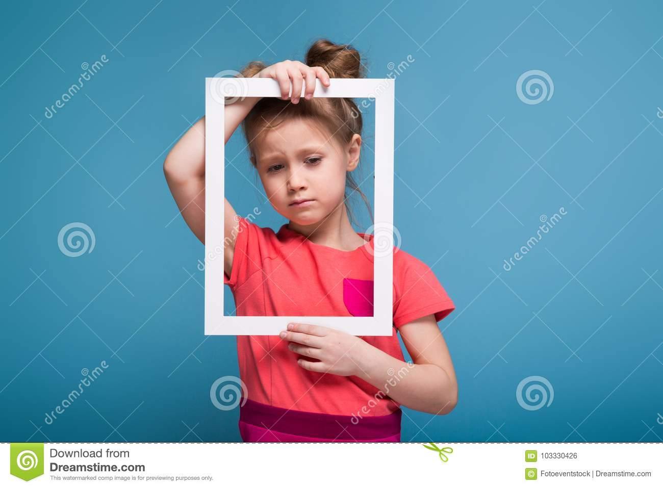 a084a7bef8c6 Isolated on blue, pretty, cute little caucasian brunette girl in pink dress  holds white picture frame, look through the frame, making sad face