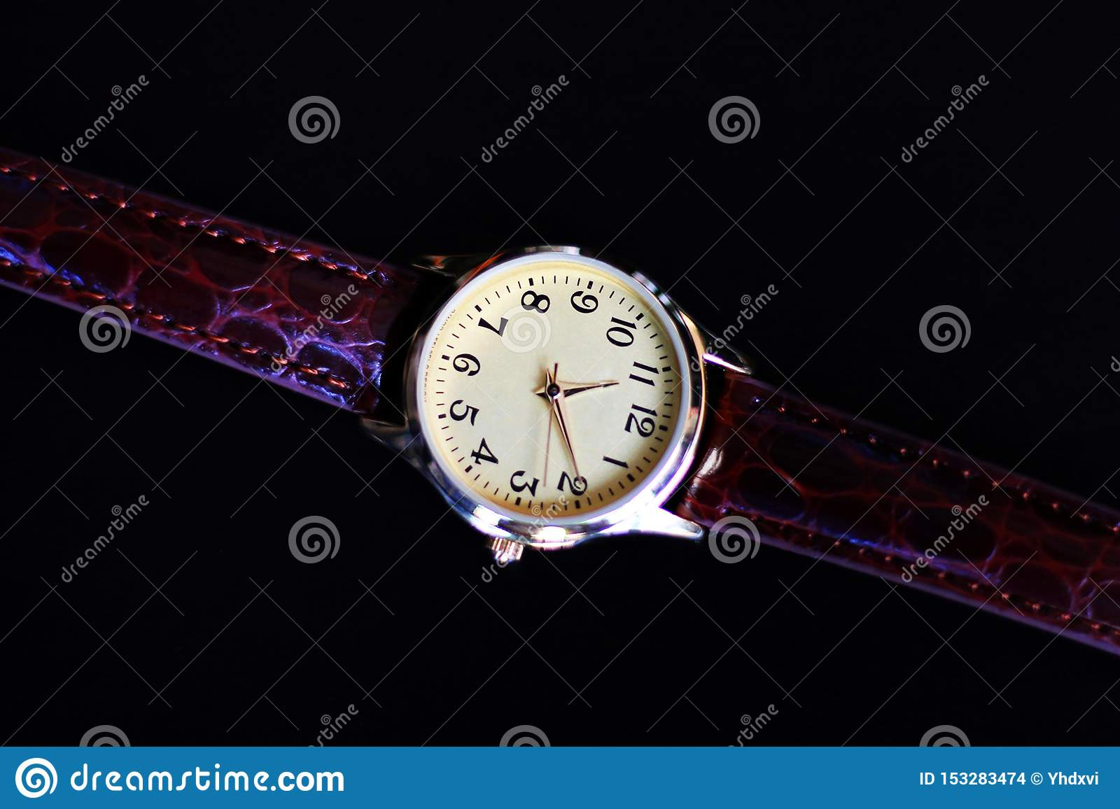 Isolated gold and quartz watch with leather strap.