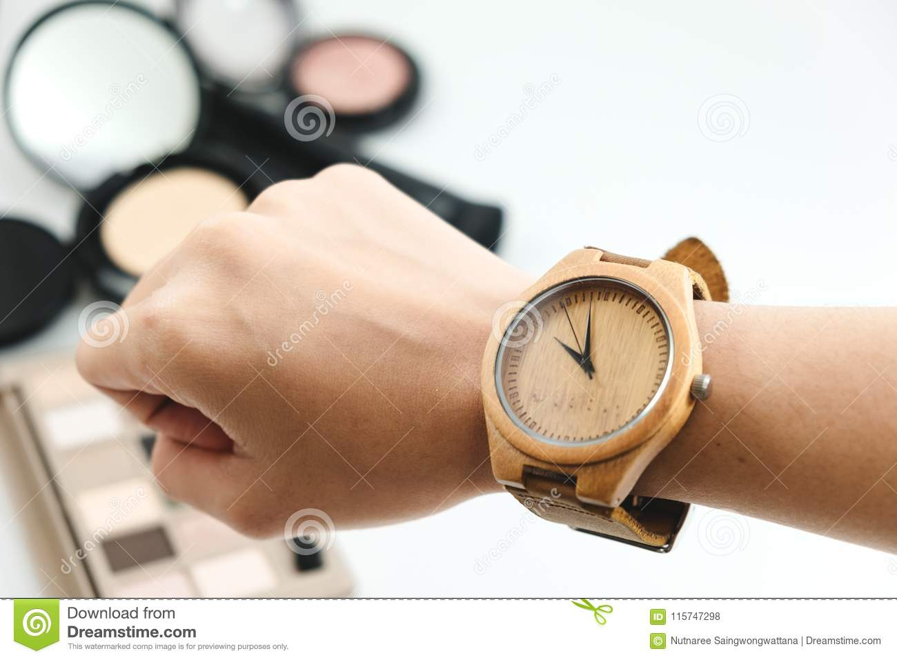 isolated hand of woman wearing wooden watch with cosmetic product, powder, brush on white background. image for copy