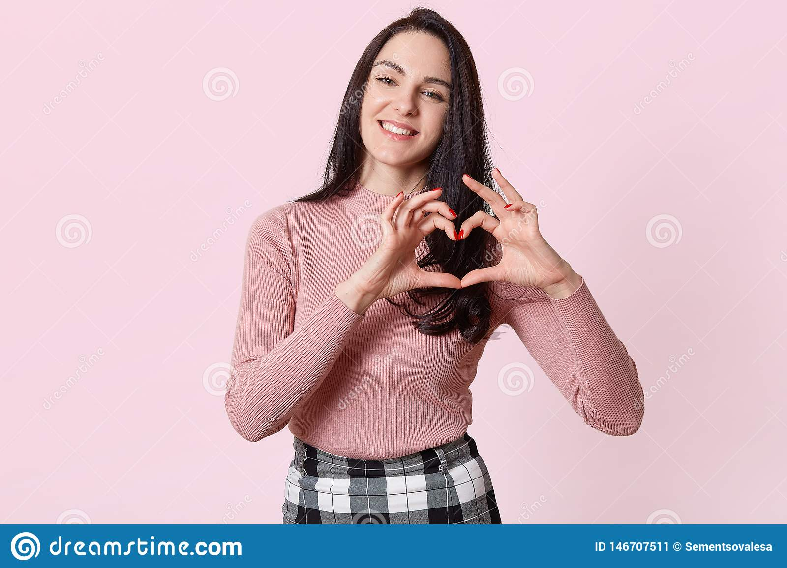 Isolated portrait of beautiful caucasian brunette female makes heart symbol by hands, has happy facial expression, wearing rosy