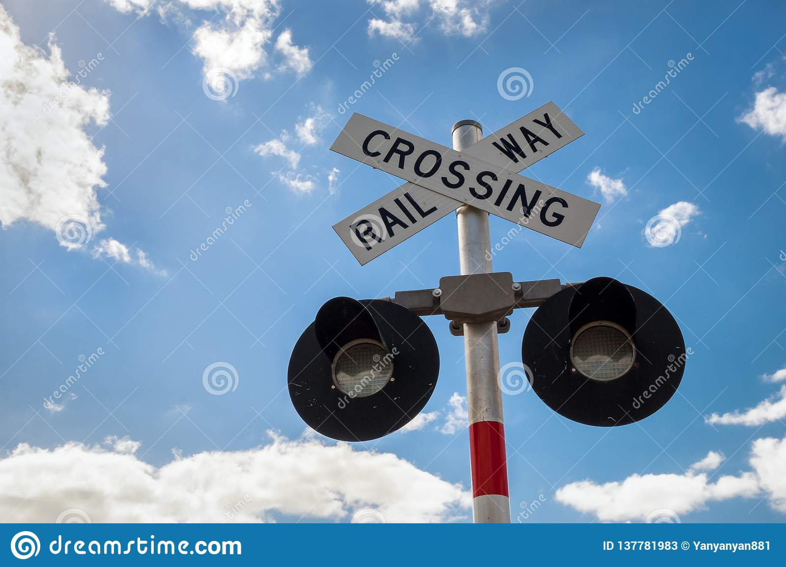 Railroad Crossing Sign with blue clear sky and white clouds. Railway crossing sign with flashing lights