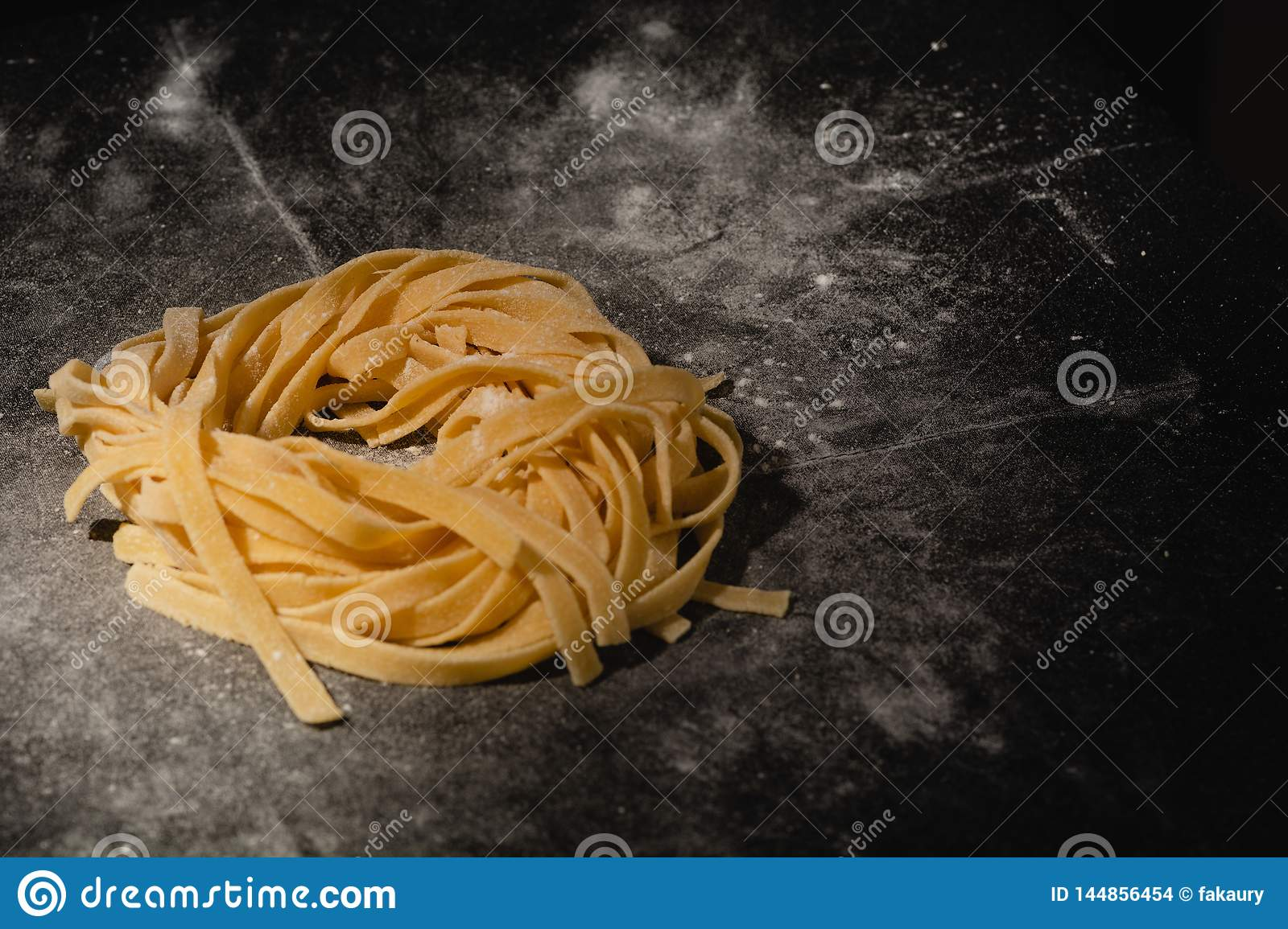 Isolated raw pasta on a black background with a place for text. Traditional Italian pasta, noodles, tagliatelle. Top view. Copy