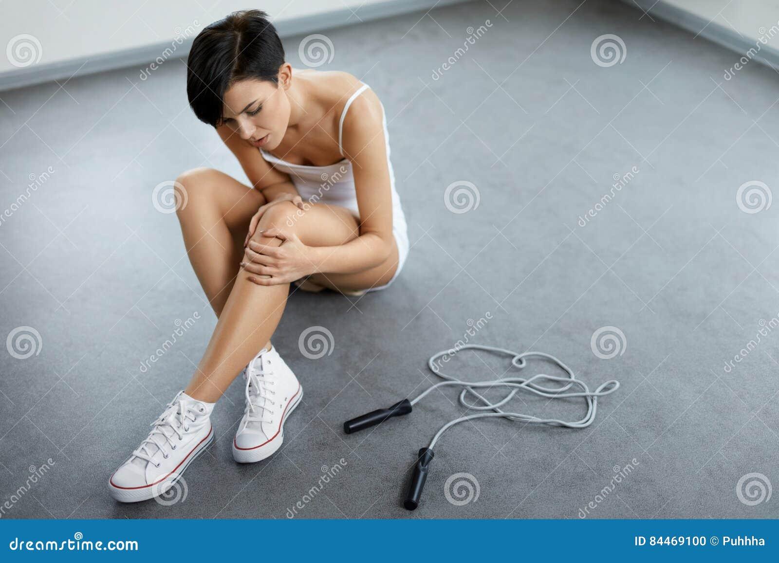 Isolerad benwhite för bakgrund skada Härlig kvinnakänsla smärtar i knäet, smärtsamt knä
