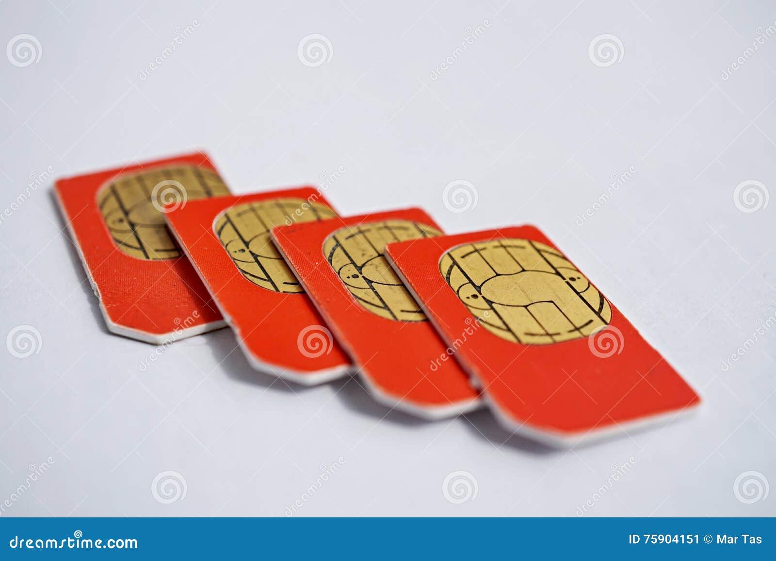 Isolerad grupp av fyra röda SIM-kort som används i mobiltelefonerna (mobiltelefon) med fokusen på guld- mikrochip