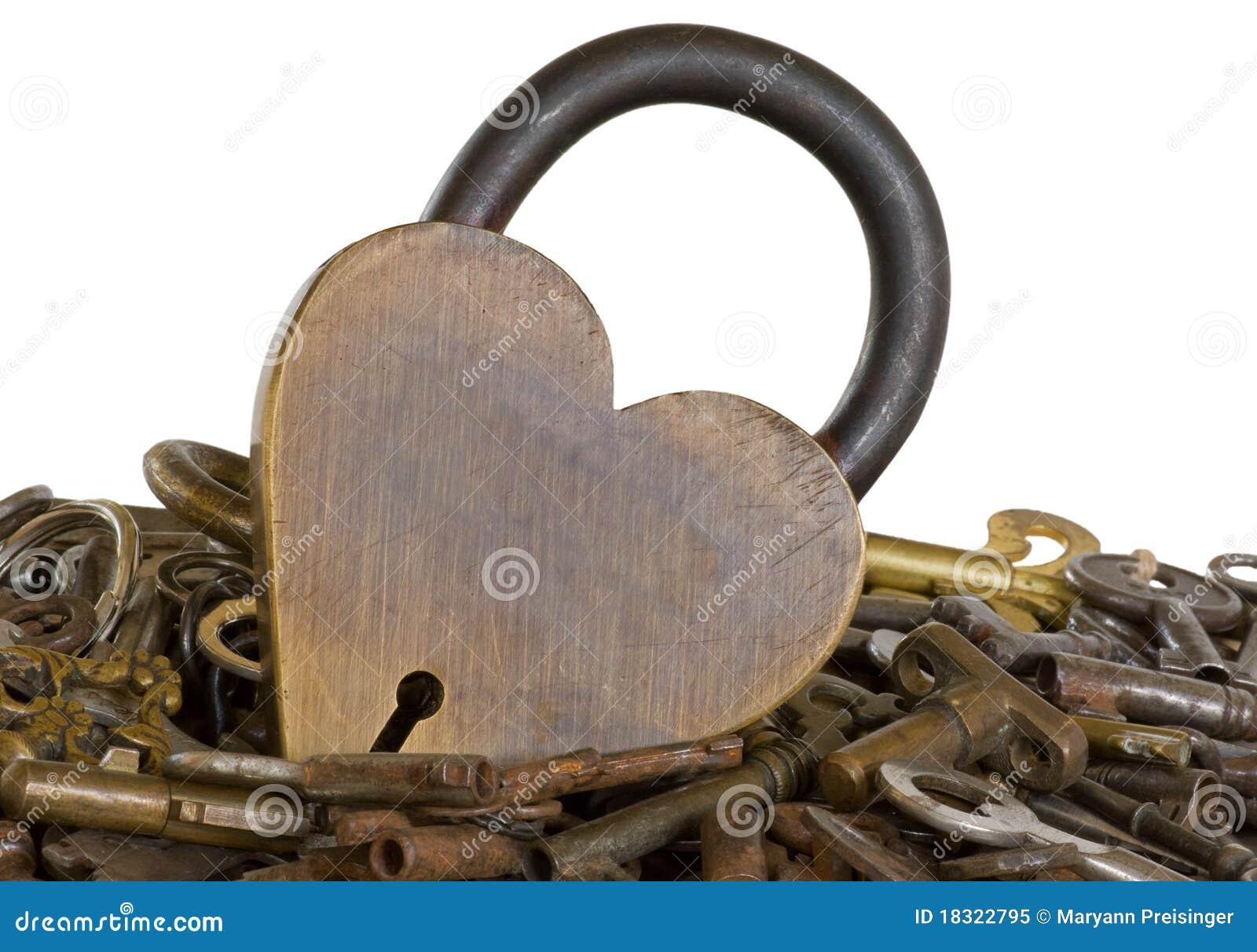 Isolerad mässingshjärta keys omgivet gammalt för lås