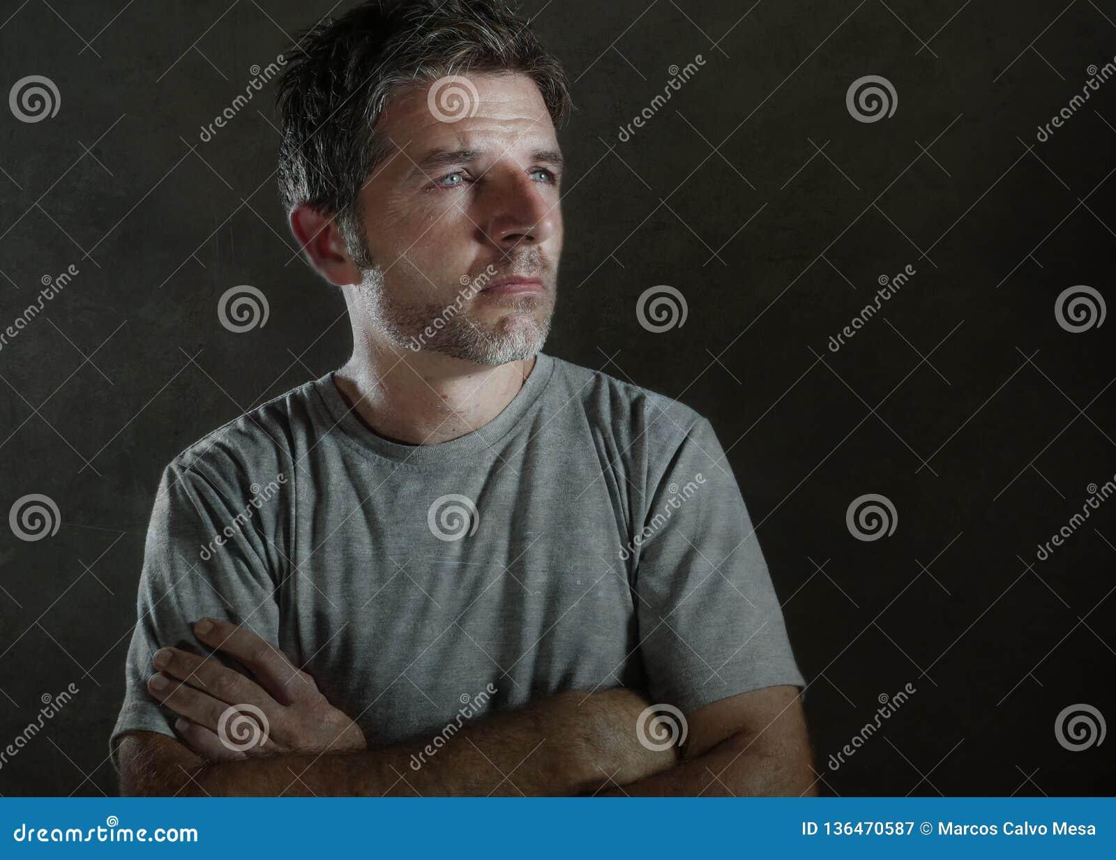 Isolerad mörk bakgrundsstående av 30-tal till den ledsna 40-tal och den deprimerade mannen som ser fundersamt och bekymrat lidand