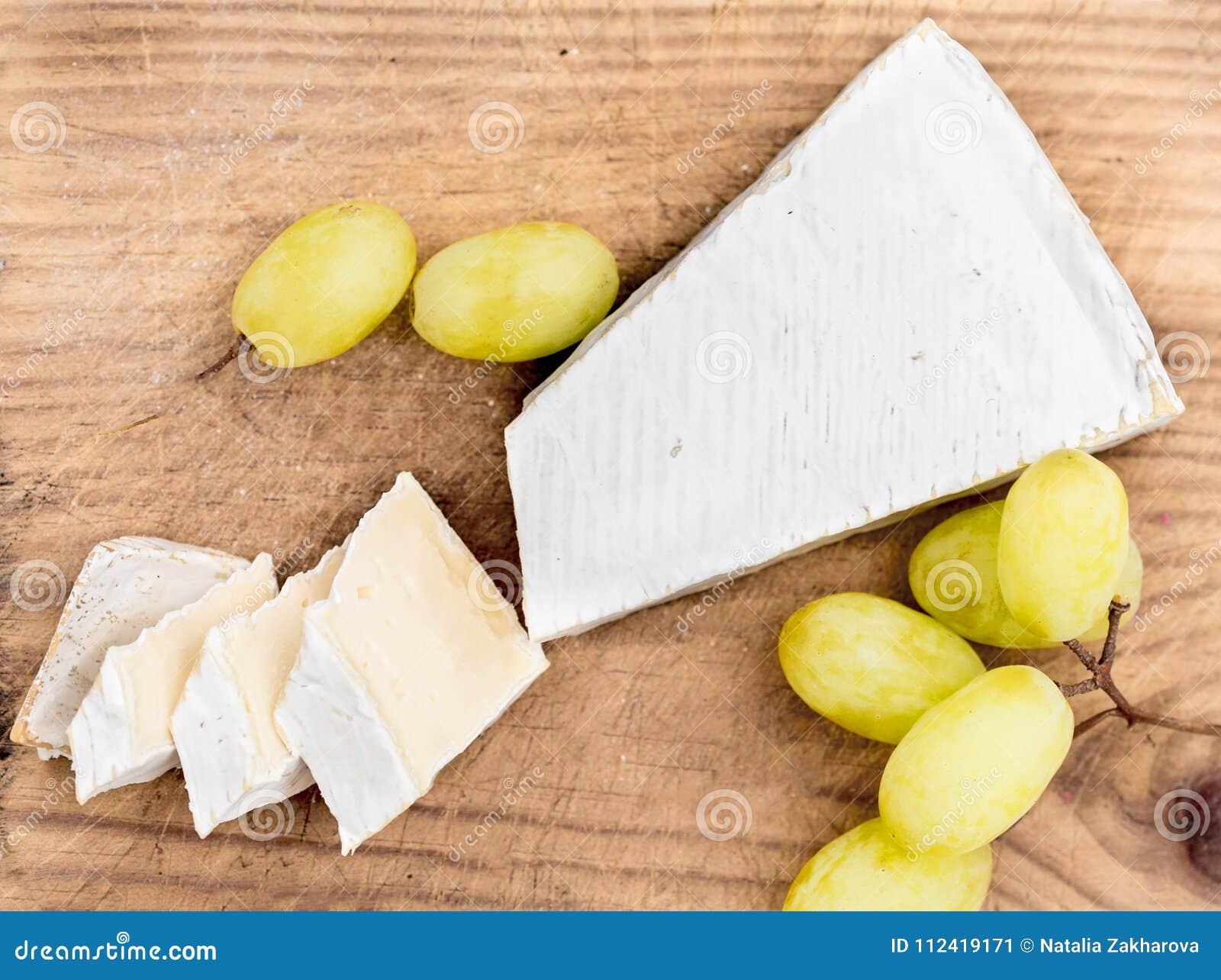 Isolerad white för bakgrundsbräde ost Krämig Brie på lantlig skärbräda över vit wo