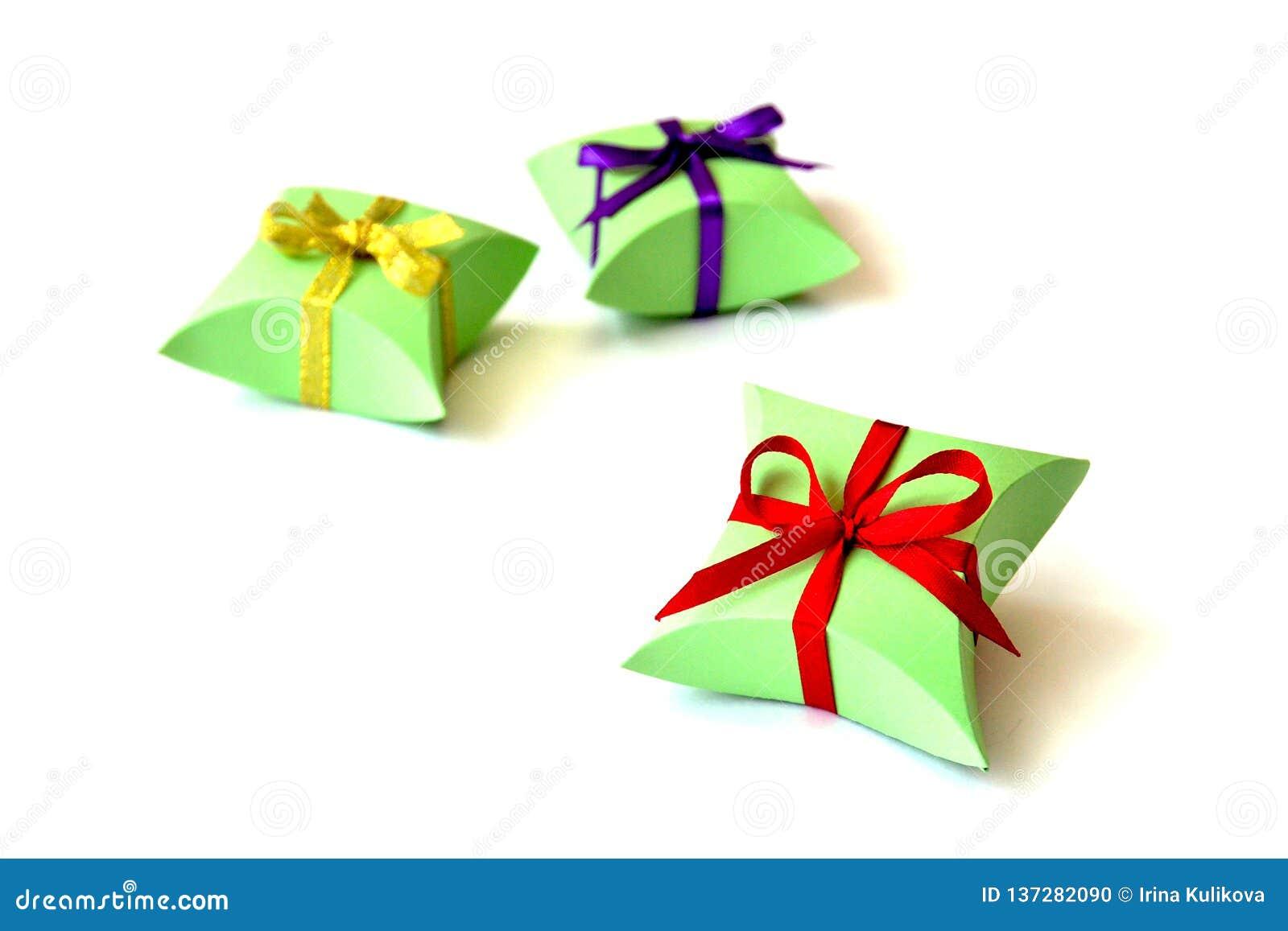 Isolerade tre askar för Apple-gräsplan pappersgåva för smycken med röda, violetta guld- satängbandpilbågar på vit bakgrund