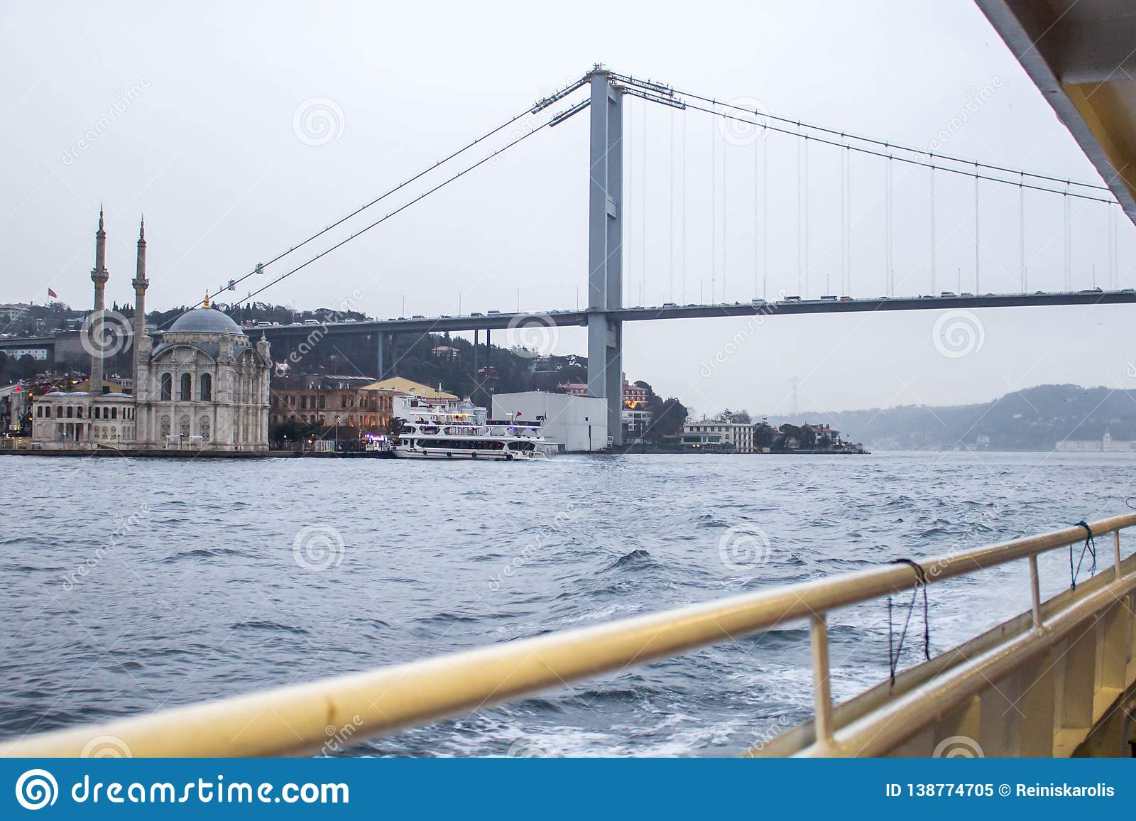 Istanbul bridge and mosque from river boat in cloudy afternoon.