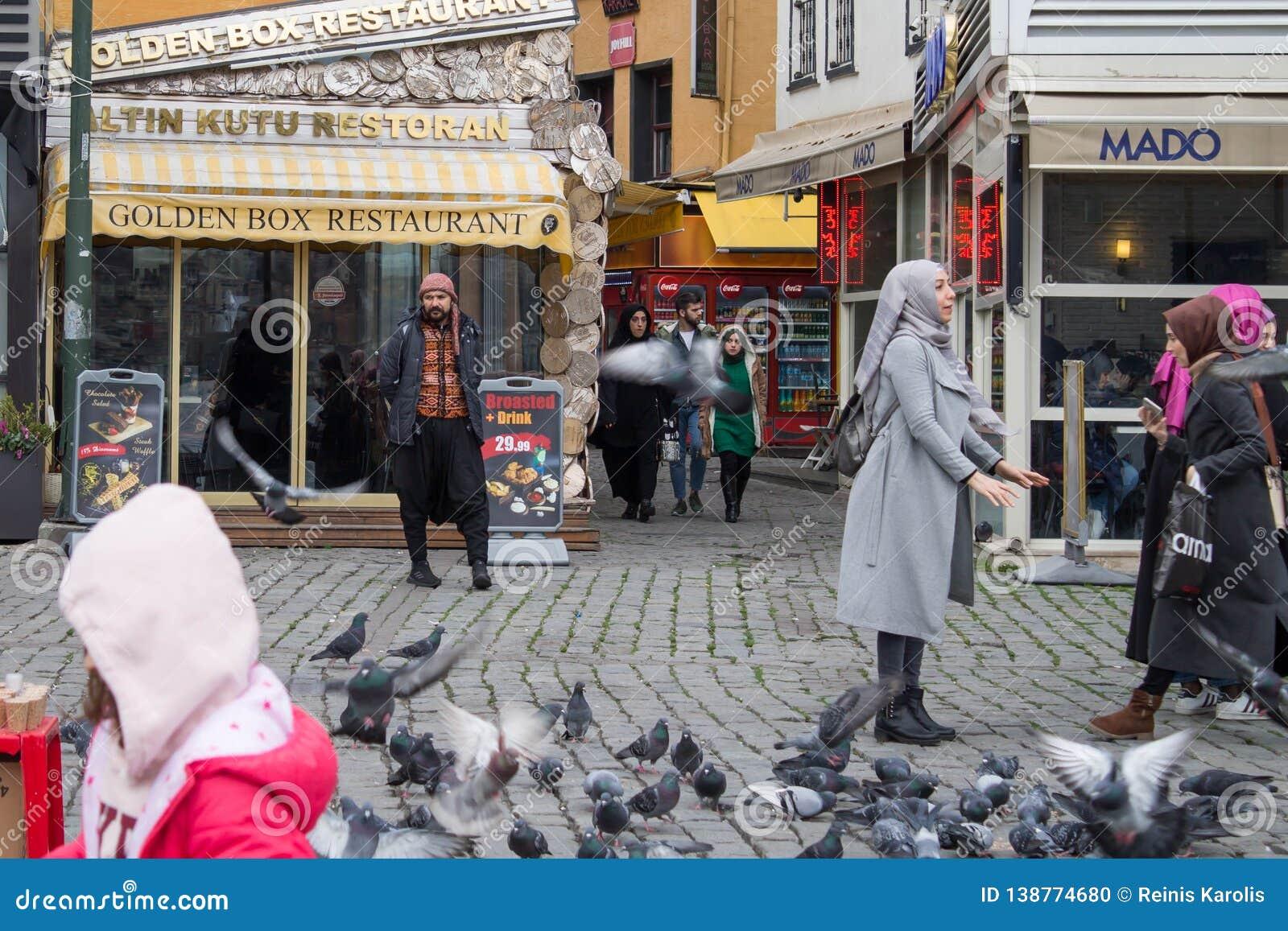 Istanbul die Türkei - 31. Januar 2019: Ein Mann annonciert Restaurant, während Leute Tauben einziehen und fangen
