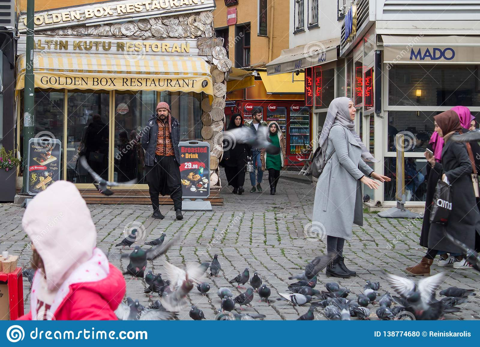 Istanbul Turkey - January 31 2019: A man is advertising restaurant while people feed and catch pigeons.