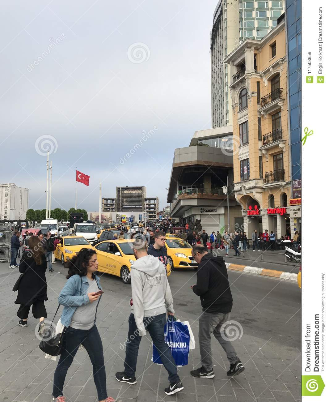 People walking around and cars in traffic at Taksim Square, Istanbul