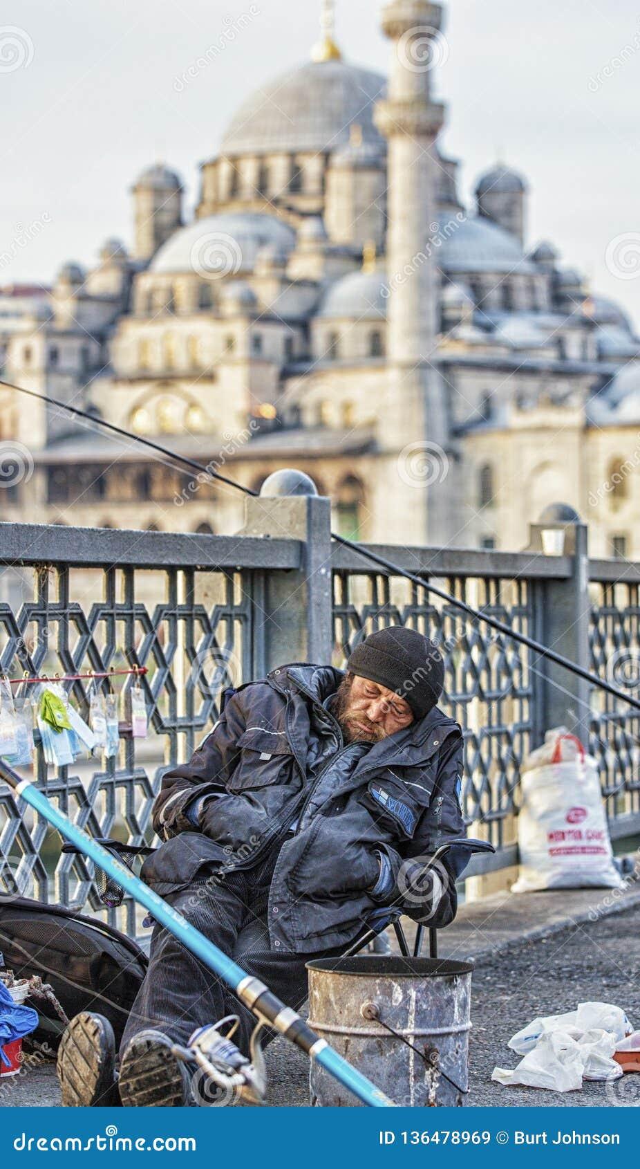 Istanbul Turkiet/April 1, 2016 - mannen sover, medan fiska av bron