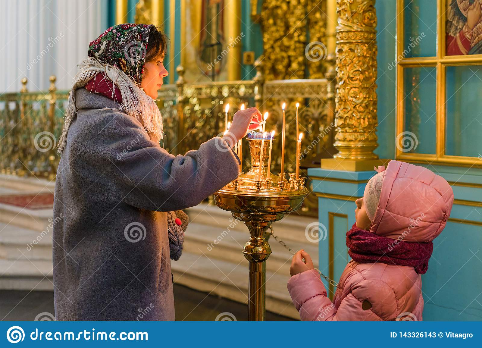 ISTRA, RUSSIA - March 23, 2019: The New Jerusalem Monastery. Young woman and her daughter put candles in the candlestick