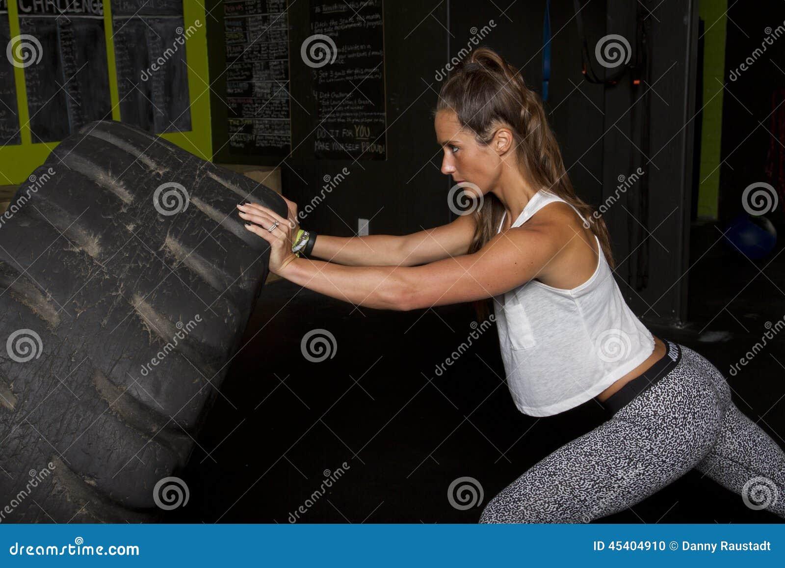 Istruttore femminile di forma fisica con la gomma pesante del trattore
