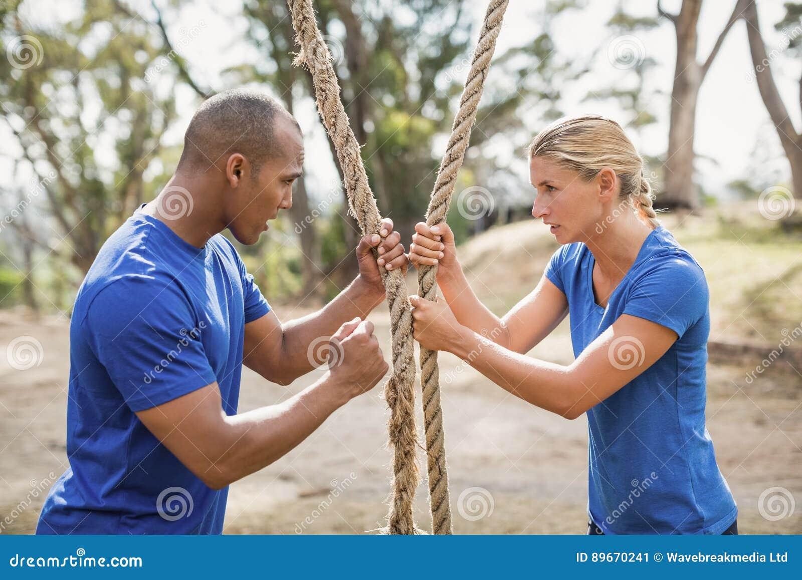 Istruttore maschio che assiste donna nella corda che scala durante la corsa ad ostacoli