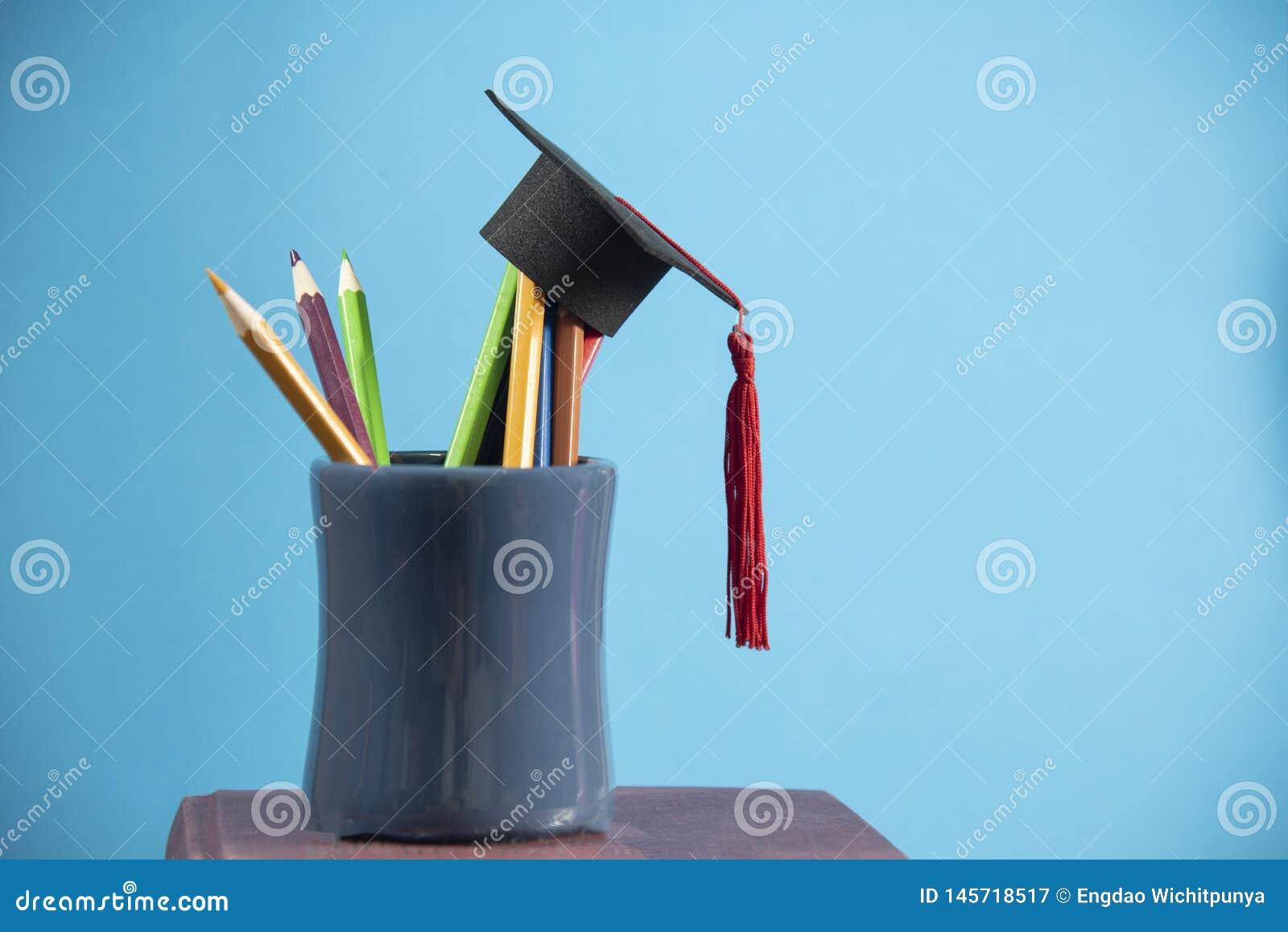 Istruzione e di nuovo al concetto della scuola con colore delle matite del cappuccio di graduazione in un astuccio per le matite