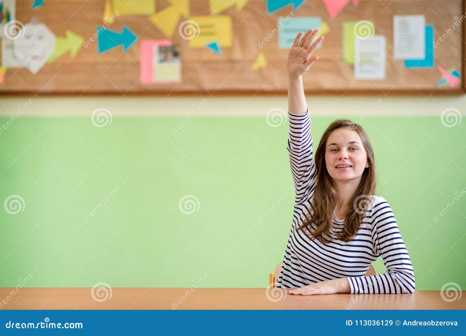 Istruzione, imparare e concetto degli adolescenti Studente che si siede nell aula e che solleva mano