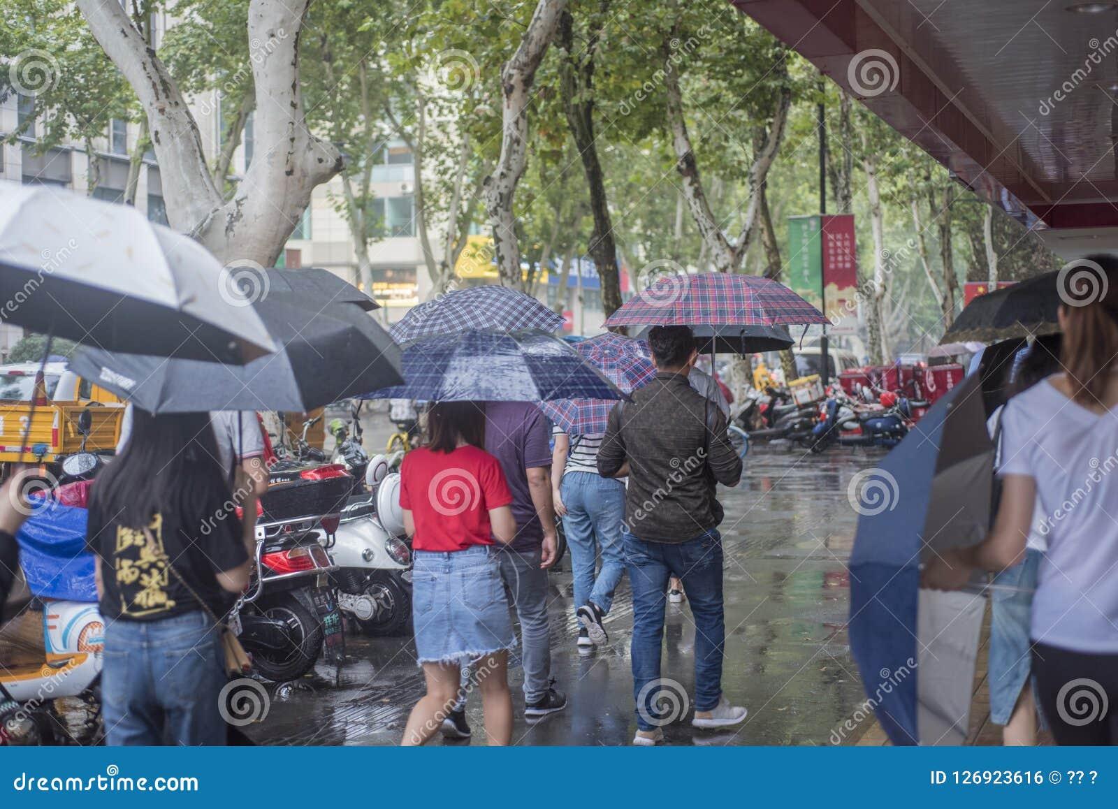 It's, das morgens regnen, und die Fußgänger, die durch die Straße gehen, überschreiten durch den Schnitt