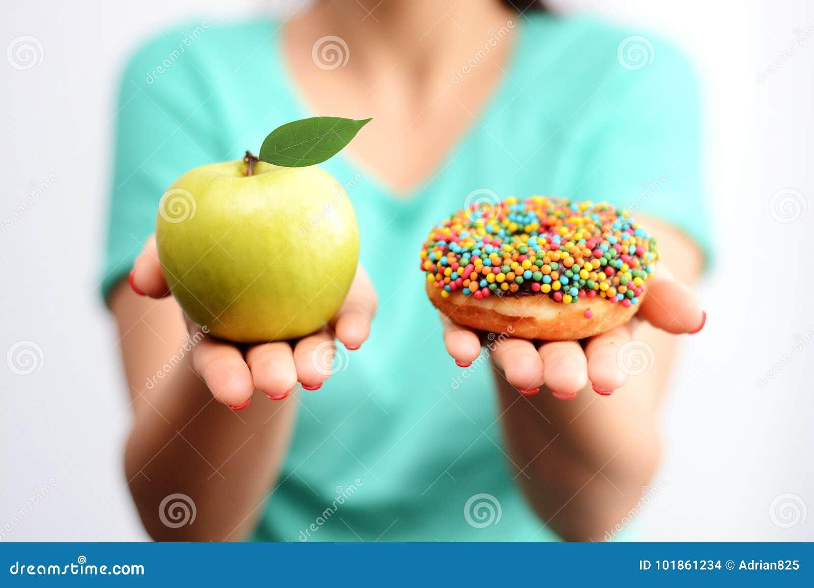 It's difícilmente para elegir concepto sano de la comida, con la mano de la mujer sosteniendo una manzana verde y un buñuelo de