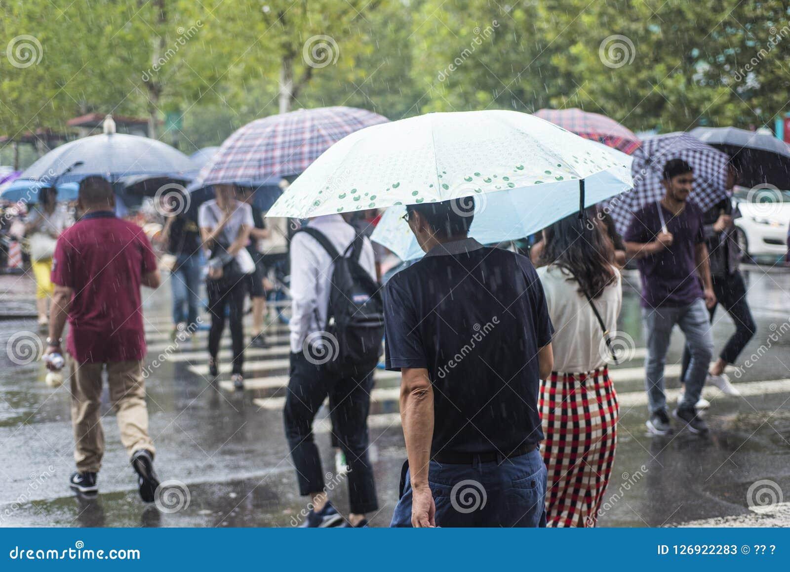 It's que llueve por la mañana, y los peatones que caminan a través del camino pasan por la intersección
