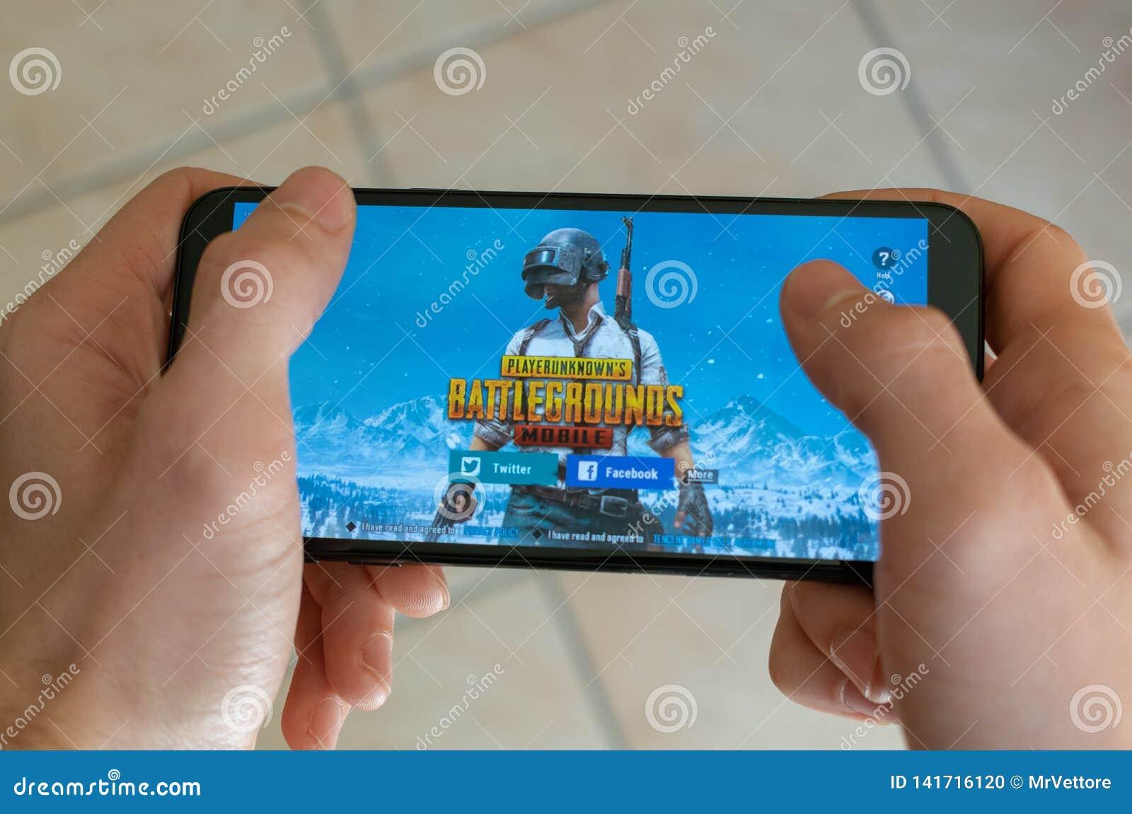 Italia, Roma - 7 de marzo de 2019: Manos que sostienen un smartphone con el juego móvil de los campos de batalla de PUBG en la pa