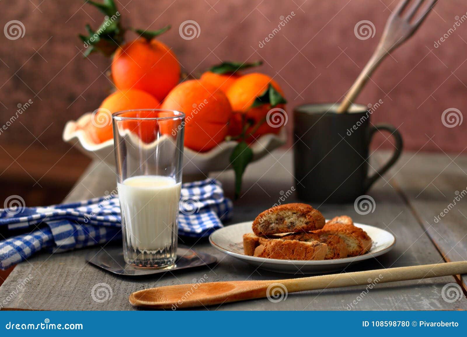 Italiaans ontbijt met melk, koekjes en sinaasappelen