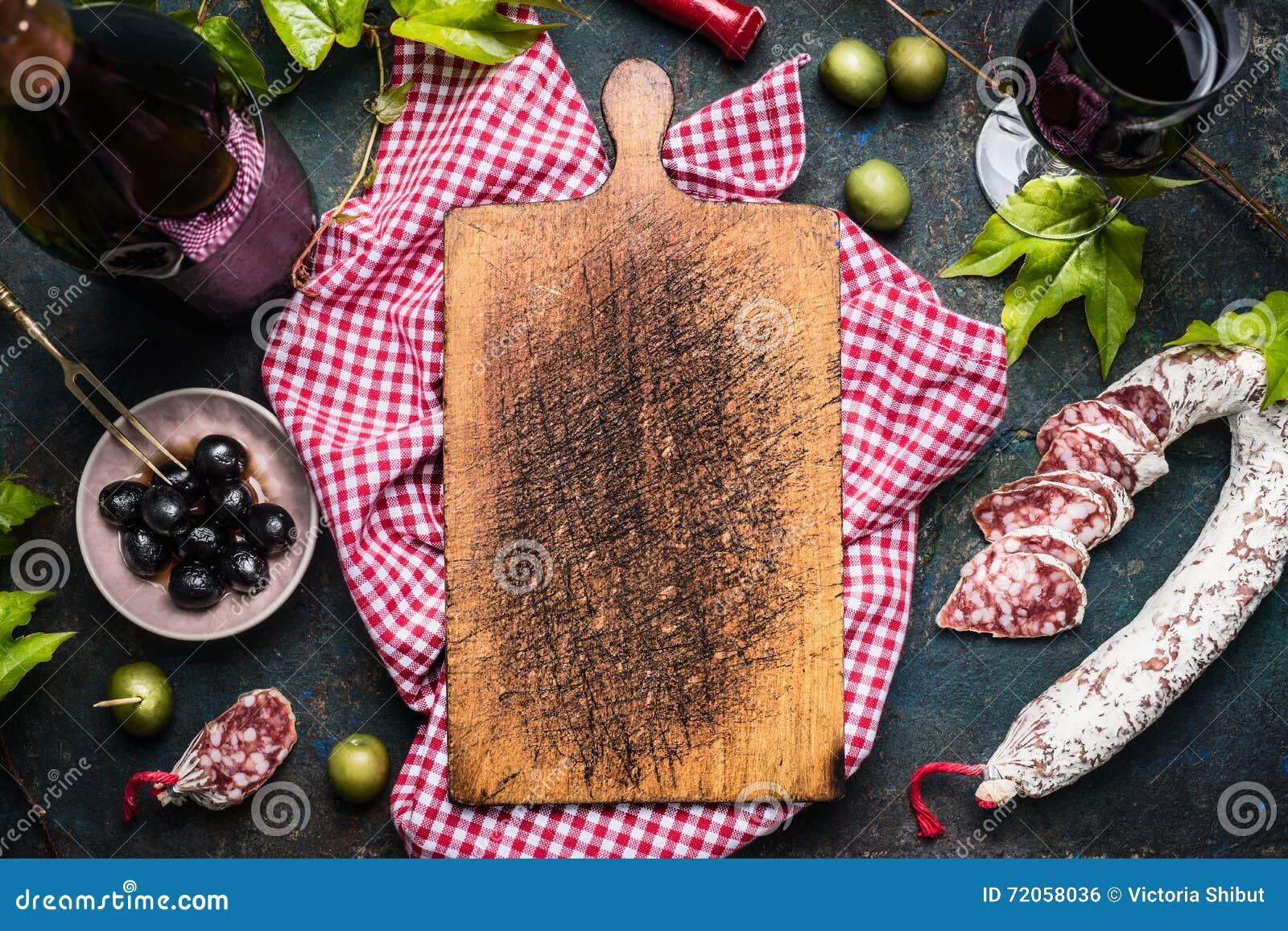 Italiaanse antipasti met olijven, rode wijn en salami rond lege oude scherpe raad, hoogste mening