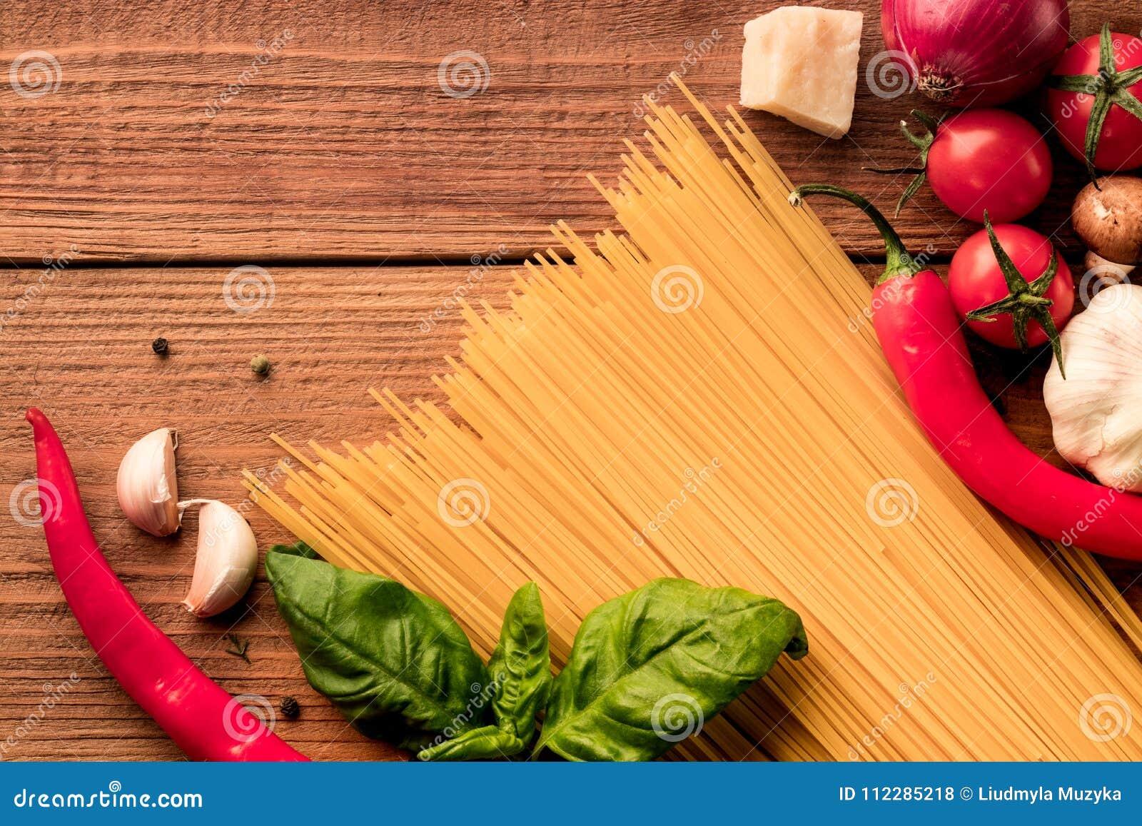Italiaanse deegwarenspaghetti met verse groenten en kruiden - hoogste mening over houten achtergrond