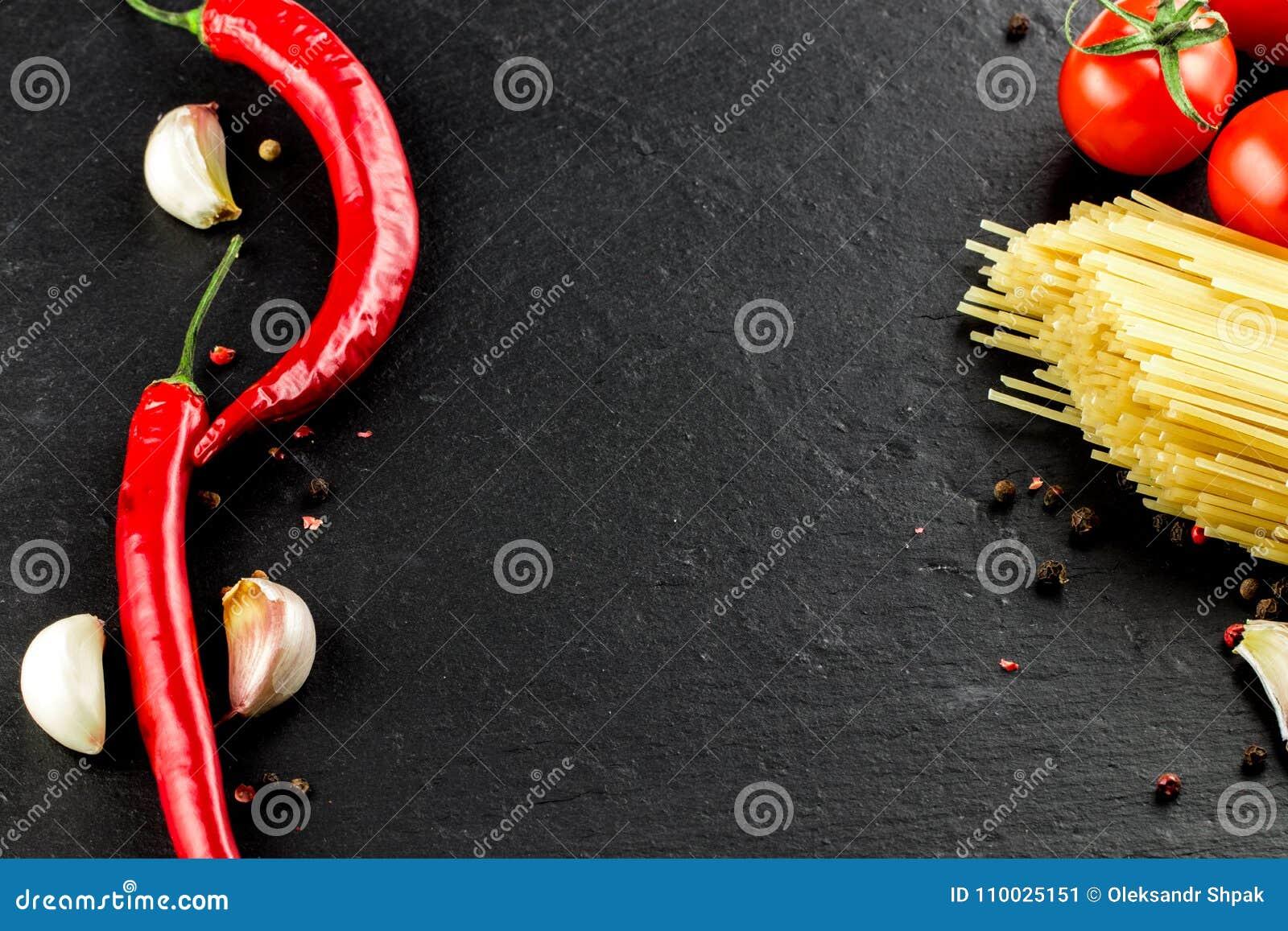 Italiaanse keuken Groenten, kruiden en deegwaren op donkere backgroun