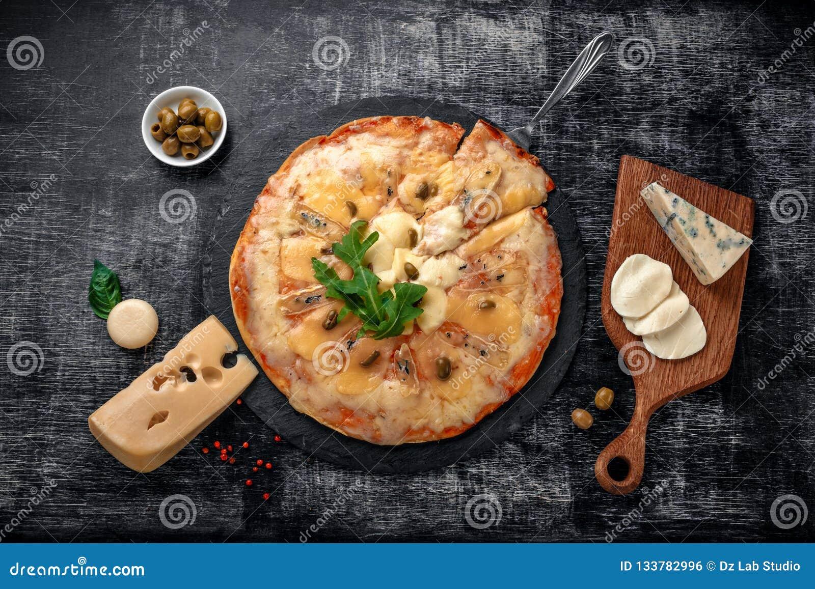 Italiaanse pizza met verschillende soorten kaas op een steen en een zwart gekrast schoolbord Italiaans traditioneel voedsel