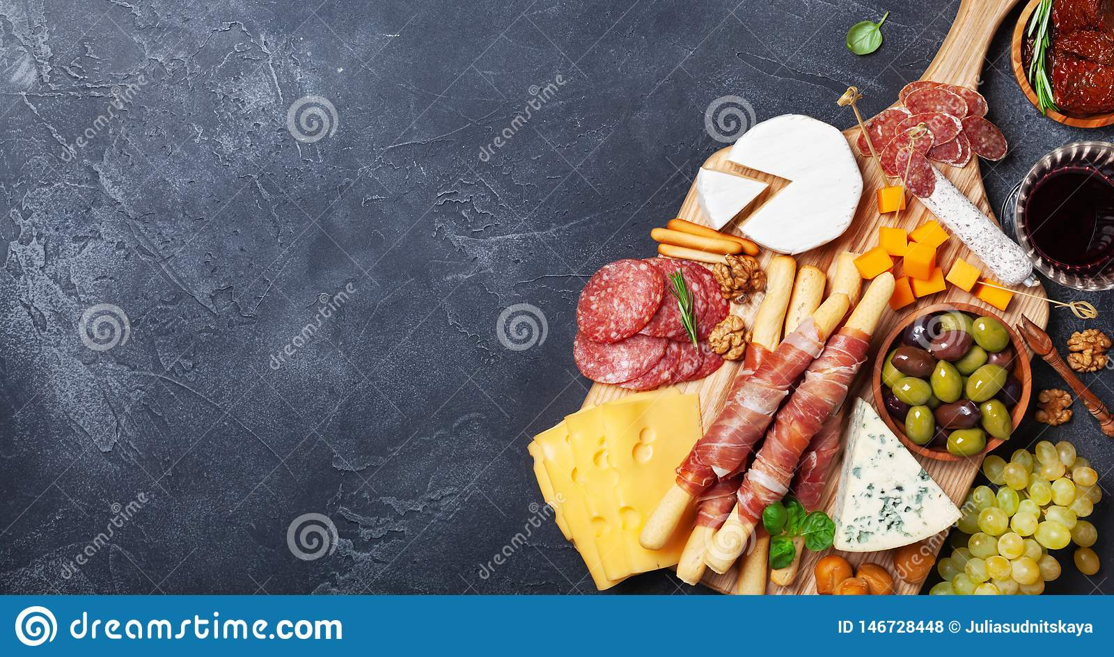 Italian appetizers or antipasto set with gourmet food on black stone table top view. Mixed delicatessen of cheese and meat snacks.
