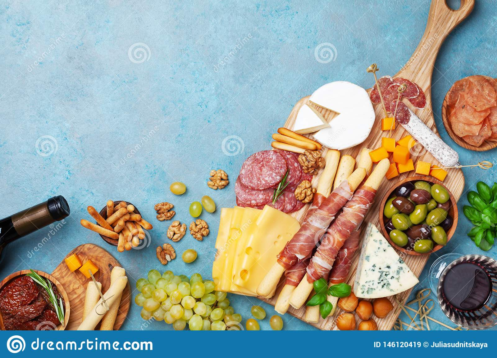 Italian appetizers or antipasto set with gourmet food on table top view. Mixed delicatessen of cheese and meat snacks with wine