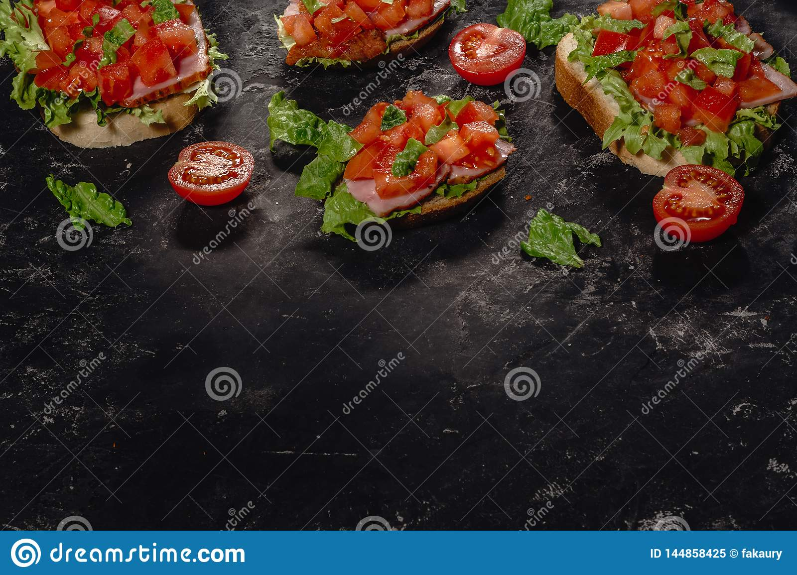Italian Bruschetta with chopped tomatoes, mozzarella sauce and salad leaves. Traditional italian appetizer or snack, antipasto.