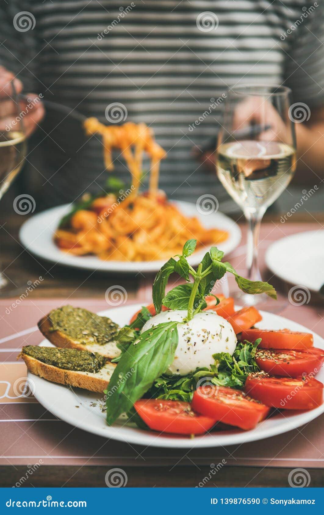 La Cuisine De Bistrot italian dinner at bistrot with caprese and pasta stock photo
