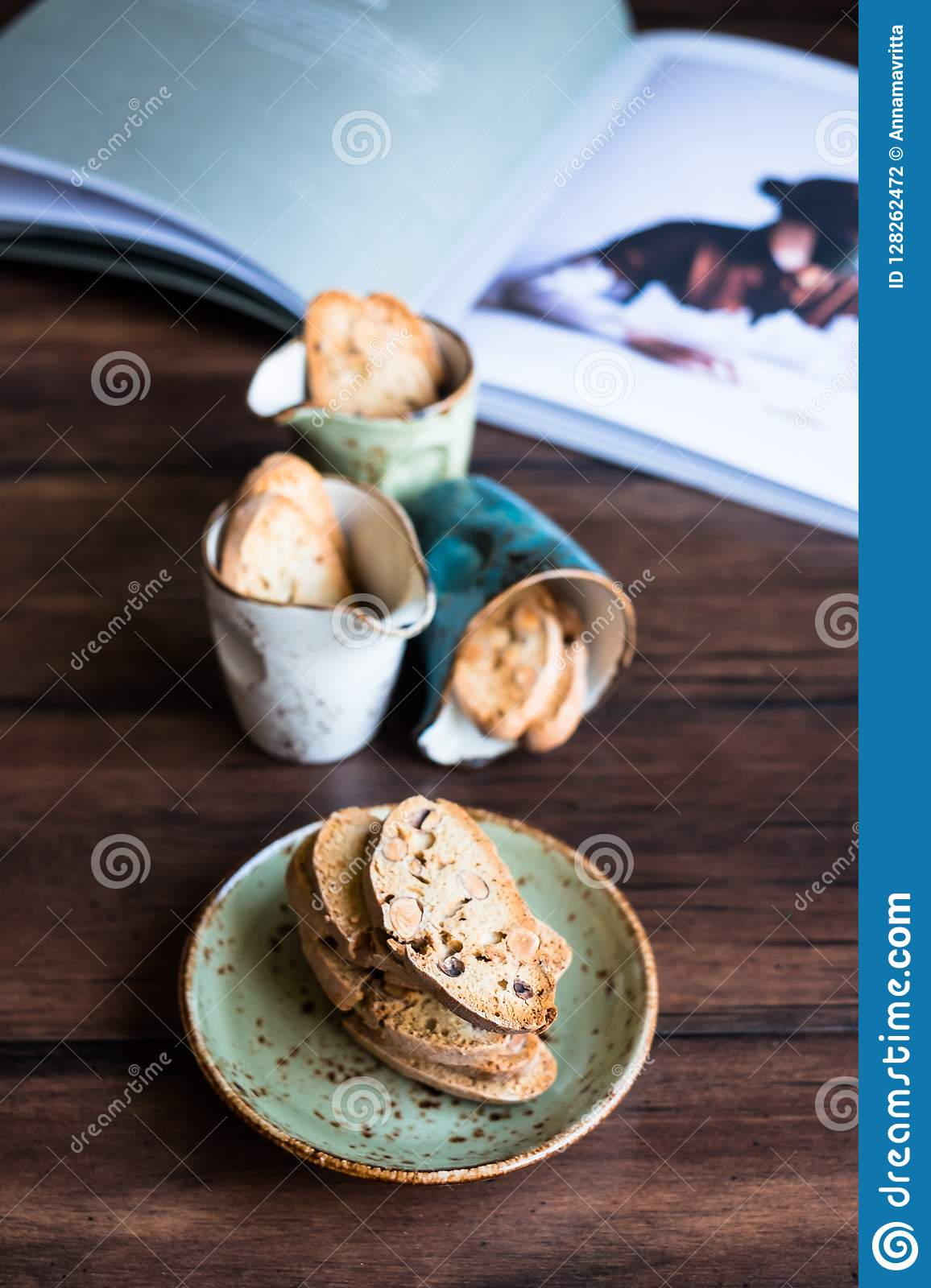 Italian dry cookies cantucci or biscotti with almond nuts stacked on a dessert plate on a wooden table, selective focus. Image wit