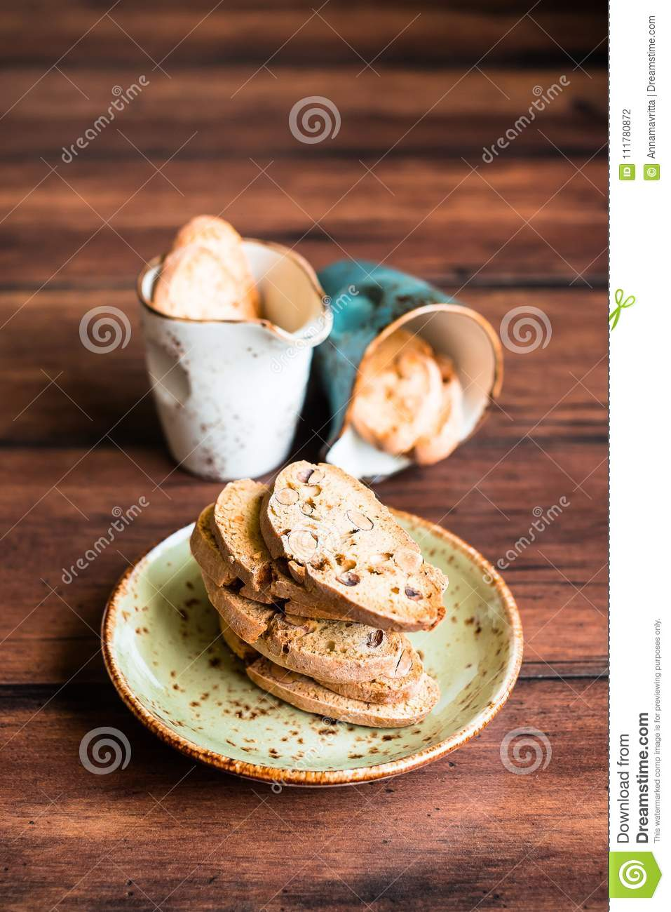 Italian dry cookies cantucci or biscotti with almond nuts stacked on a dessert plate on a wooden table, selective focus.