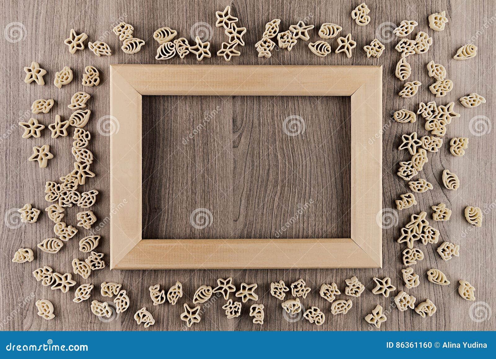 italian dry sea pasta on beige brown wooden board with empty copy