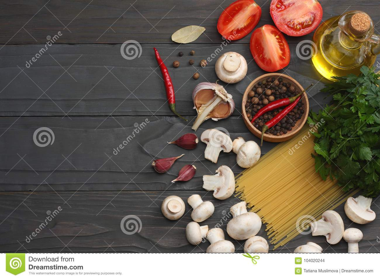 Italian food background, with tomatoes, parsley, spaghetti, mushrooms, oil, lemon, peppercorns on dark wooden table. Top view