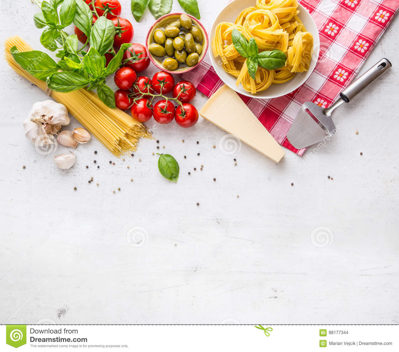 Italian food cuisine and ingredients on white concrete table. Spaghetti Tagliatelle olives olive oil tomatoes parmesan cheese.