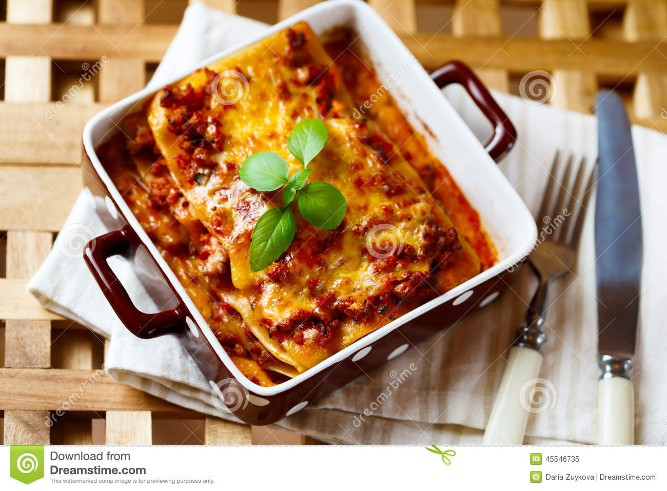 ... Lasagna plate served with fresh basil leaf on wooden table. Top view