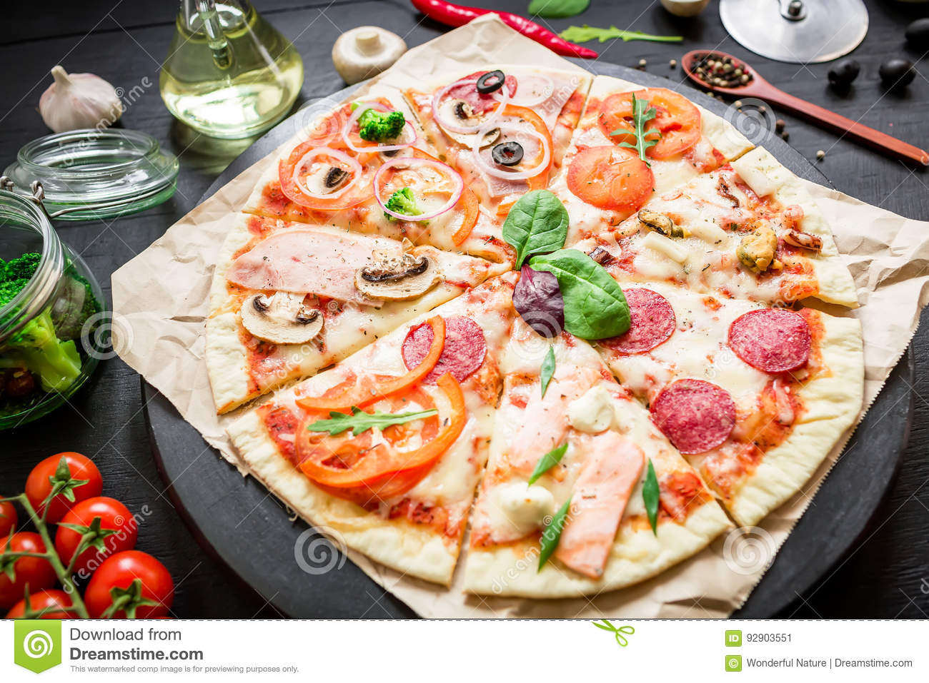 Italian food. Pizza with ingredients, spices, oil and vegetables on dark background. Flat lay, top view.